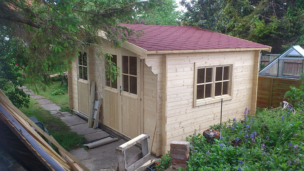 Lukas log cabin with a shed attached